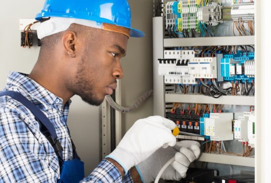 Young African Male Technician Repairing Fusebox With Screwdriver