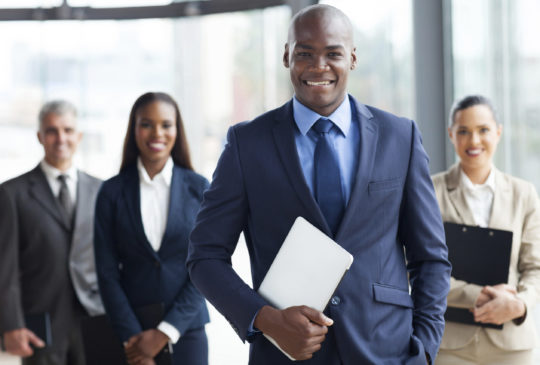 handsome african businessman with group of businesspeople on background